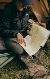 photo-of-woman-sitting-while-pointing-on-world-map-2422483